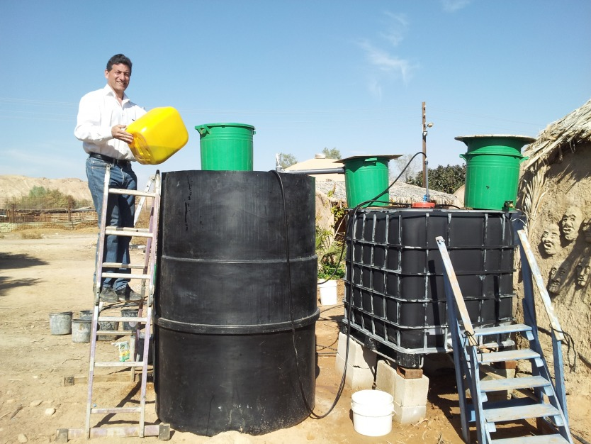 Culhane innoculates the ARTI side of the Solar CITIES IBC/ARTI hybrid with cow manure from the Kibbutz